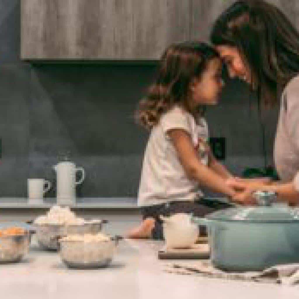 Mother and daughter with daughter sitting on the kitchen counter