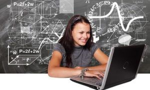 Young Lady on the Laptop Getting tons of Ideas seem on the chalk board behind her