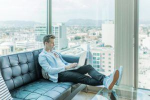 Man in a high rise apartment work online with a laptop