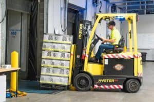 A Yellow Hyster forklift being used by driver to load a 53' foot trailer
