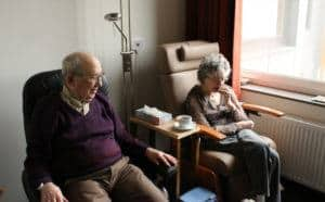 Senior Elderly Couple sitting in chairs in a hospital room setting