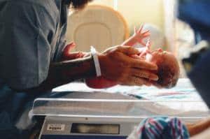 Nurse putting a newborn in Bassinet