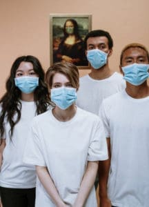 Medical workers training two female and two male students wearing blue hospital face mask