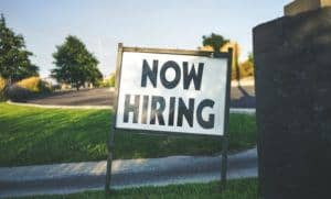 Now Hiring sign place in the grass. with white background